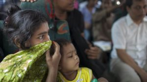 Woman holds material over nose and mouth on public bus in Dhaka